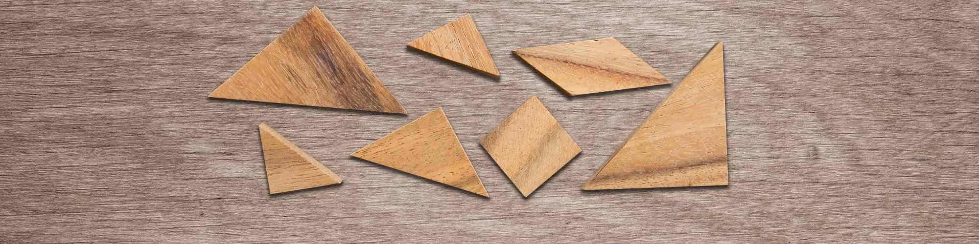 Tangram Steine liegen ungeordnet auf einer Holzplatte